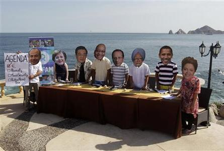 Oxfam activists wear masks representing some of the G20 world leaders, sitting at a dinner table along the shore in Los Cabos June 17, 2012. G20 leaders will kick off two days of meetings in the Pacific resort of Los Cabos on Monday. REUTERS/Andres Stapff