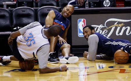 Oklahoma City Thunder's Kevin Durant (L), Derek Fisher (C), and Lazar Hayward (R) joke as they stretch during a team practice for the NBA basketball finals in Miami June 18, 2012. REUTERS/Mike Segar