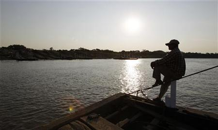 A man looks at the sunset by the Mamore river some 15 km from Trinidad, August 15, 2011. REUTERS/David Mercado/Files