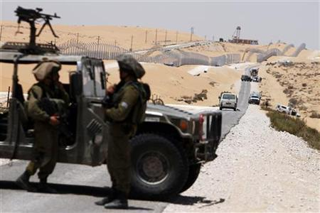 Israeli security forces survey the scene of an attack by militants near the southern Israeli village of Kadesh Barnea, along Israel's border with Egypt's Sinai desert June 18, 2012. REUTERS/Amir Cohen