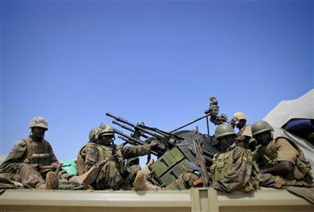 Ugandan soldiers serving African Union Mission in Somalia (AMISOM) sit in the back of a truck mounted with an anti-aircraft gun as they pass over open ground on outskirts of Afgoye, west of Mogadishu, May 24, 2012. REUTERS/Stuart Price/African Union-United Nations Information Support Team/Handout