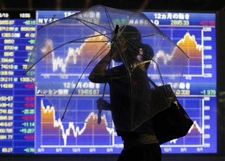 A woman with an umbrella walks in a heavy rain caused by Typoon Guchol in front of an electronic board displaying graphs of market indices outside a brokerage in Tokyo June 19, 2012. REUTERS/Issei Kato