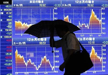 A man in front of a board showing the graph of the change of the exchange rate between the foreign currencies and Japanese Yen for the last 12 months outside a brokerage in Tokyo June 19, 2012. REUTERS/Issei Kato