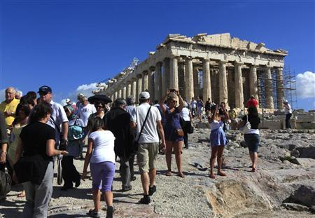 Foreign tourists visit the Parthenon atop Athens' Acropolis hill October 15, 2010. REUTERS/Yannis Behrakis