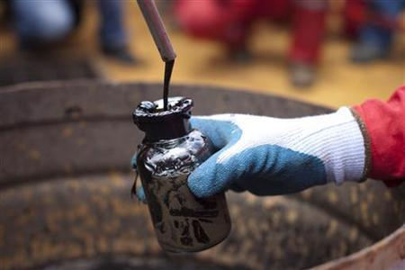 A worker collects crude oil sample at an oil well operated by Venezuela's state oil company PDVSA in Morichal July 28, 2011. REUTERS/Carlos Garcia Rawlins
