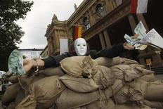 A protester holds fake money next to a wall of sandbags built during a protest against financial speculations in front of Frankfurt's stock exchange June 17, 2012. REUTERS/Alex Domanski