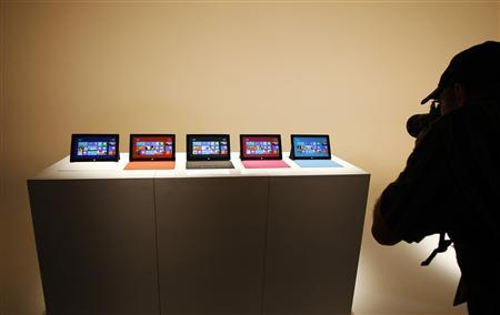 A photographer takes pictures of new Microsoft Surface tablet computers on display at its unveiling in Los Angeles, California, June 18, 2012. Microsoft Corp introduced its own line of tablet computers on Monday at a media event in Los Angeles, marking a major strategic shift for the software giant as it struggles to compete with Apple Inc and re-invent its aging Windows franchise. REUTERS/David McNew