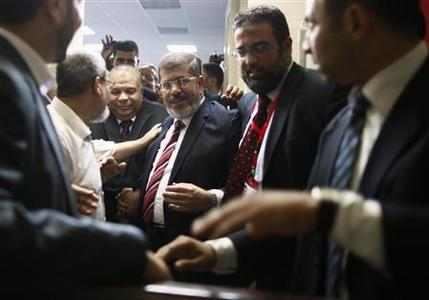 Muslim Brotherhood's presidential candidate Mohamed Morsy (C) leaves after a news conference in Cairo June 18, 2012. Egypt's Muslim Brotherhood declared on Monday that its candidate Morsy won the country's first free presidential race, beating Hosni Mubarak's last prime minister and ending six decades of rule by presidents plucked from the military. REUTERS-Suhaib Salem
