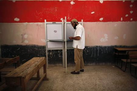 A voter prepares to cast his vote at a polling station in Cairo June 17, 2012. A second day of voting on Sunday will deliver Egypt's first freely elected president, though the country faces renewed tension whether he is a former general from the old guard or an Islamist from the long-suppressed Muslim Brotherhood. REUTERS-Ahmed Jadallah