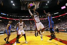 Miami Heat forward LeBron James (C) shoots as Oklahoma City Thunder forward Kevin Durant (R) defends in the first half during Game 4 of the NBA basketball finals in Miami, Florida, June 19, 2012. REUTERS/Mike Ehrmann/POOL