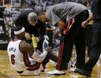 Miami Heat forward LeBron James is helped by teammates and trainers after being injured in the fourth quarter against the Oklahoma City Thunder during Game 4 of the NBA basketball finals in Miami, Florida, June 19, 2012. REUTERS/Mike Segar