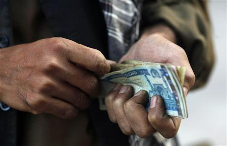 A vendor counts his earnings of the day in front of a branch of the Kabulbank in Kabul September 14, 2010. REUTERS/Andrew Biraj