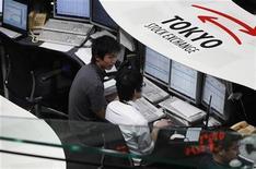 Сотрудники Токийской фондовой биржи следят за рынком 18 июня 2012 года. Азиатские фондовые рынки, кроме Китая, выросли благодаря надежде инвесторов на новые стимулирующие меры ФРС США. REUTERS/Yuriko Nakao