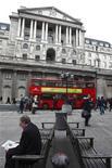 Мужчина сидит перед входом в Банк Англии в Лондоне, 24 марта 2010 года. Банк Англии практически готов одобрить новый этап монетарных стимулов, а его управляющий Мервин Кинг выступает за расширение выкупа облигаций на 50 миллиардов фунтов, показал протокол заседания Центробанка от 6-7 июня. REUTERS/Darrin Zammit Lupi