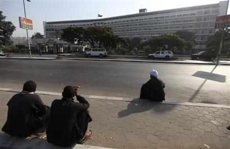 People sit in front of Maadi military hospital where Egypt's ousted president Hosni Mubarak was transferred from Tora prison, on the outskirts of Cairo June 20, 2012. Ousted Egyptian president Hosni Mubarak was moved from prison to a military hospital on Tuesday after a health crisis, officials said. Senior officers and military sources gave various accounts of the 84-year-old Mubarak's condition, including that he was in a coma and on life support. But they said he was not ''clinically dead,'' as briefly reported by the state news agency. REUTERS/Amr Abdallah Dalsh
