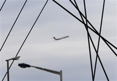 A Japan Airlines aircraft is seen behind the wires of a bridge at Haneda airport in Tokyo June 20, 2012. Japan Airlines (JAL) is expected to apply as early as Wednesday to re-list its shares in September after raising about $8 billion in an initial public offering, doubling the government's investment in a rare successful case of state-led restructuring in Japan. REUTERS/Kim Kyung-Hoon