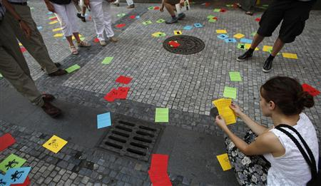 A woman reads a leaflet during a protest rally in support of the detained members of the Russian all-girl punk rock band Pussy Riot in Prague June 19, 2012. REUTERS/David W Cerny