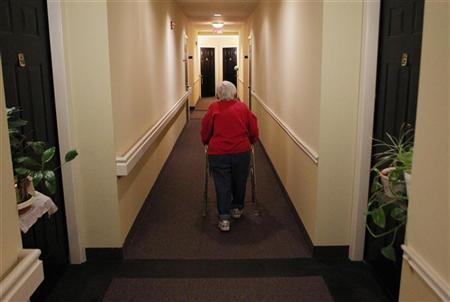 A senior walks down the hallway with the aide of her walker to visit a neighbor at her independent living complex in Silver Spring, Maryland April 11, 2012. REUTERS/Gary Cameron