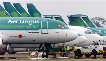 Ground crew are seen parking an Aer Lingus Airbus A320 away from the passenger terminals at Dublin Airport, in the Republic of Ireland, June 2, 2002. REUTERS/Paul McErlane/Files