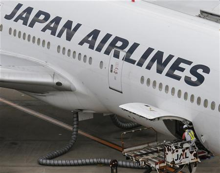 An employee of Japan Airlines (bottom, R)works on an aircraft at Haneda airport in Tokyo June 20, 2012. REUTERS/Kim Kyung-Hoon