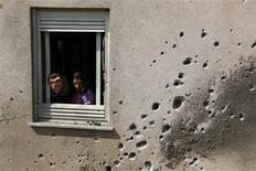 Israeli woman look out the window of a house damaged after a rocket fired by Palestinian militants in Gaza landed in Kibbutz Sa'ad outside the central Gaza Strip June 20, 2012. Israel killed a Gaza militant on Wednesday as a surge of fighting across the border of the Palestinian enclave entered a third day despite what Egypt said were its efforts to broker a truce. REUTERS/Amir Cohen