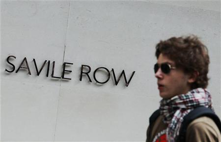 A man passes a Savile Row sign, in London August 21, 2010. REUTERS/Luke MacGregor