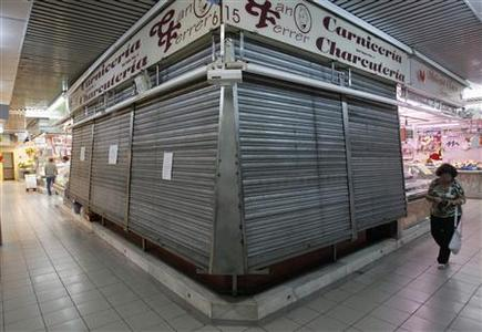 A woman walks pass a foreclosed stall at El Masnou's market, near Barcelona, June 19, 2012. REUTERS/Albert Gea