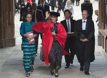 Myanmar pro-democracy leader Aung San Suu Kyi leaves through The Great Gate after receiving her honorary degree at Oxford University, in Oxford southern England June 20, 2012. Myanmar's Nobel laureate Aung San Suu Kyi on Wednesday continued an emotional visit to Britain, where she left her family 24 years ago and took up her famous struggle against the military dictatorship in her homeland. REUTERS/Ki Price
