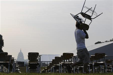 A worker puts the finishing touches to an art installation of 857 empty school desks at the National Mall, near the Washington Monument, in Washington June 20, 2012. REUTERS/Jonathan Ernst