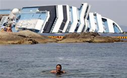 A woman swims in front of the wreckage of capsized cruise liner Costa Concordia near the harbour of Giglio Porto June 20, 2012. Salvage crews began preliminary work this week on preparations to refloat the half-submerged Costa Concordia cruise liner in what is set to be the biggest ever operation of its kind. REUTERS/Max Rossi