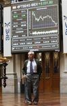 El Ibex-35 cerró el miércoles al alza, por encima de otros mercados europeos, apoyado en los valores bancarios y constructores y con los inversores tomando posiciones ante la reunión de la Fed de Estados Unidos que podría decidir esta tarde nuevos estímulos monetarios para impulsar la economía. En la imagen, un operador junto a un panel electrónico en la Bolsa de Madrid, el 19 de junio de 2012. REUTERS/Andrea Comas