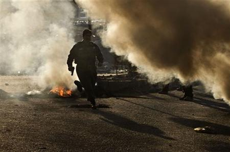 An Afghan policeman runs for cover during clashes with protesters in Kabul February 24, 2012. REUTERS/Ahmad Masood/Files