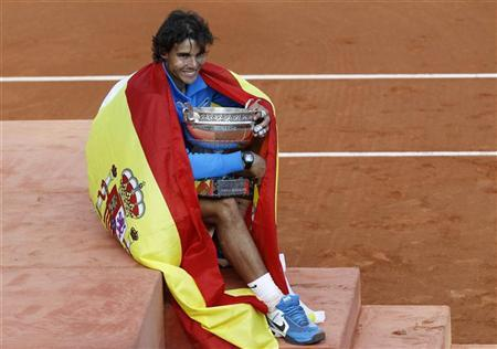 Rafael Nadal of Spain poses with the trophy and the Spanish flag during the ceremony after defeating Roger Federer of Switzerland during their men's final at the French Open tennis tournament at the Roland Garros stadium in Paris June 5, 2011. REUTERS/Thierry Roge