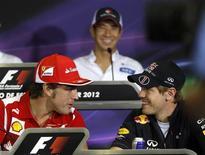 """Fernando Alonso (esquerda), da Ferrari, e Sebastian Vettel (direita), da Red Bull, conversam em Barcelona, 10 de maio de 2012. Alonso e Vettel podem """"facilmente coexistir juntos"""" como companheiros de equipe, disse o chefe da equipe Ferrari, Stefano Domenicali. REUTERS/Gustau Nacarino"""