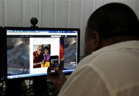 Chinese dissident artist Ai Weiwei uses his smart phone to take a photograph of a website showing a picture of the Dalai Lama and Myanmar pro-democracy leader Aung San Suu Kyi in his studio in Beijing June 20, 2012. Ai said on Wednesday police had warned him to stay away from a court hearing on his company's lawsuit against a tax agency, which he said illegally imposed a 15 million yuan ($2.4 million) tax evasion penalty on it. Beijing's Chaoyang District Court agreed last month to hear the lawsuit from the company that markets Ai's work, a departure from the courts' consistent refusal to give dissidents such as Ai any hearing. REUTERS/David Gray