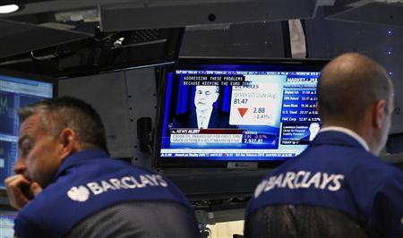 Traders work on the floor of the New York Stock Exchange, as a news conference by U.S. Federal Reserve Chairman Ben Bernanke is displayed on a screen, June 20, 2012. REUTERS/Brendan McDermid