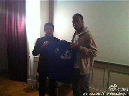 An undated handout photo shows Zhou Jun (L), director of Shanghai Shenhua Football Club, and soccer player Didier Drogba holding up a souvenir jersey of Shanghai Shenhua FC during a meeting in France. REUTERS/Shanghai Shenhua Football Club/Handout