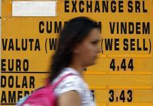 Женщина проходит мимо пункта обмена валют в Бухаресте, 11 мая 2012 года. Доллар поднялся по отношению к евро после того, как ФРС разочаровала инвесторов, воздержавшись от более активных стимулирующих мер. REUTERS/Bogdan Cristel