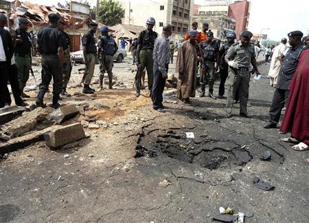 Security officials assess the scene of a bomb blast in Nigeria's northern city of Kaduna April 8, 2012. Suspected members of Nigerian Islamist sect Boko Haram have killed four people and a large undetonated bomb was found in Kano on Monday, authorities said, a day after at least 36 people were killed in a car bomb near a church in northern Kaduna. Picture taken April 8, 2012. REUTERS/Stringer