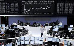 Traders work at their desks in front of the Dax board at the Frankfurt stock exchange June 20, 2012. REUTERS/Remote/Fabrizio Bensch
