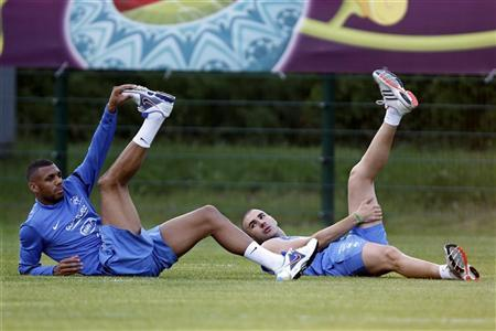 France's soccer players Yann M'Vila (L) and Karim Benzema (R) stretch during a training session at the team's training center in Kircha near Donetsk June 20, 2012. REUTERS/Charles Platiau