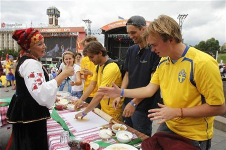 An Ukrainian women, dressed in traditional clothes, instructs Sweden soccer fans in how to make traditional Ukrainian Vareniks dumplings, at the Euro 2012 fan zone in central in Kiev June 15, 2012. REUTERS/Gleb Garanich