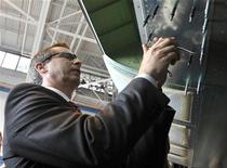 Ontario Premier Dalton McGuinty installs a rivet on a Global 6000 aircraft during a tour of Bombardier's manufacturing facilities in Toronto May 29, 2012. REUTERS/ Mike Cassese