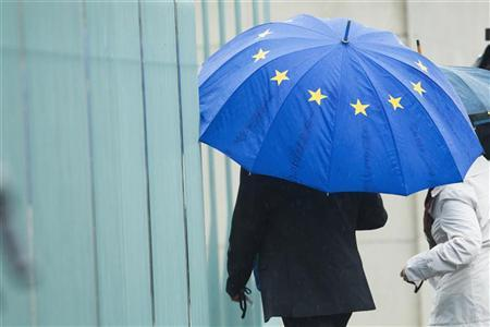 A man holding an umbrella in the colours of the European Union enters the chancellery in Berlin before talks between government and opposition leaders about the EU fiscal pact June 21, 2012. REUTERS/Thomas Peter