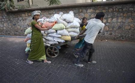 Labourers pull a cart loaded with cement sacks down a street in Mumbai May 20, 2011. REUTERS/Vivek Prakash/Files