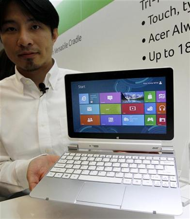 An employee displays Acer's Iconia W510 touch pad during a news conference on which Acer introduces its new tablets and ultrabooks with Microsoft Windows 8 operation system as part of the preview of the 2012 Computex exhibition at the Taipei International Convention Center in Taipei June 4, 2012. REUTERS/Pichi Chuang