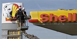 Активисты Greenpeace вешают баннер с полярным медведем на АЗС Shell в Праге 10 мая 2012 года. Сто мировых знаменитостей поддержали в четверг кампанию Greenpeace против бурения нефтяных скважин и избыточной рыбной ловли в Арктике, где мировой нефтегазовый гигант Shell планирует разведочное бурение. REUTERS/David W Cerny