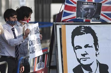 Protesters supporting Wikileaks founder Julian Assange hold placards outside the Supreme Court in London May 30, 2012. REUTERS/ Ki Price