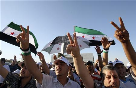 People shout slogans in support of Colonel Hassan Hamada, a Syrian air force pilot who flew his MiG-21 fighter plane over the border to Jordan on Thursday, during a demonstration against Syria's President Bashar al-Assad outside the Syrian embassy in Amman June 21, 2012. REUTERS/Ali Jarekji