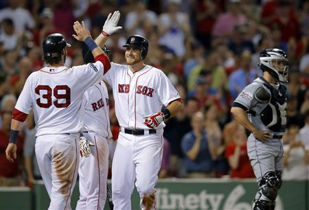 Boston Red Sox Jarrod Saltalamacchia (39) and Will Middlebrooks (C) celebrate beside Miami Marlins catcher Brett Hayes after scoring on Middlebrooks' two-run home run in the eighth inning of their MLB interleague baseball game at Fenway Park in Boston, Massachusetts June 21, 2012. REUTERS/Brian Snyder